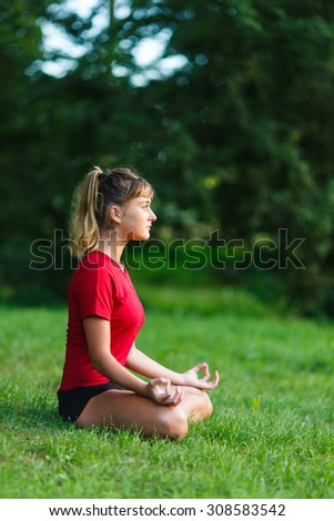 Cute young girl doing yoga exercises outdoor