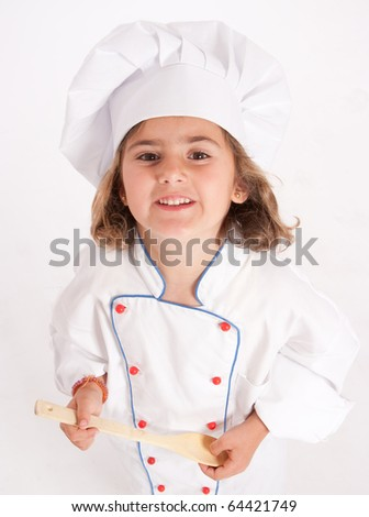 Cute young girl dressed as a chef with a spoon looking up - stock photo