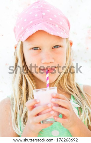 Cute young girl drinking milk fruit smoothie with striped straw from glass held in hands - stock photo