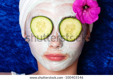 Cute young girl getting pampered with a deluxe spa treatment including facial mask and sliced cucumber over her eyes. - stock photo
