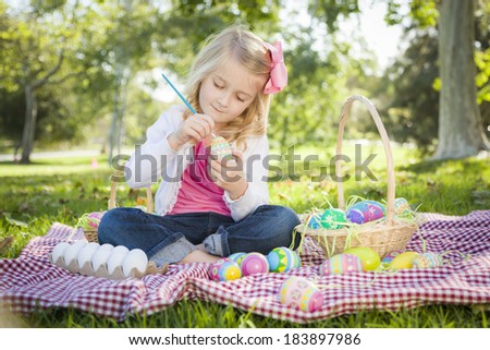Cute Young Girl Happily Coloring Her Easter Eggs with Paint Brush in the Park. - stock photo