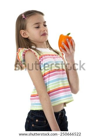 Cute young girl holding orange bell pepper, on white background. - stock photo
