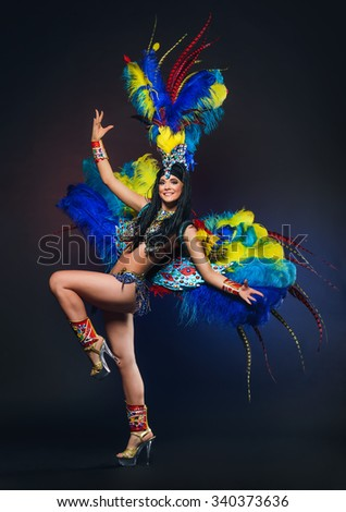 Cute young girl in bright colorful carnival costume on dark background - stock photo