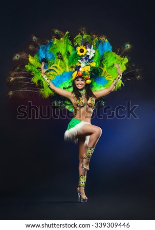 Cute young girl in green carnival costume on dark background - stock photo