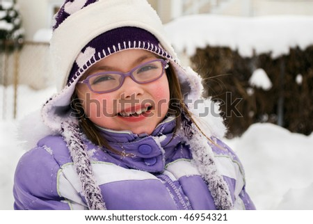 cute young girl in purple jacket laughing and playing in the snow - stock photo