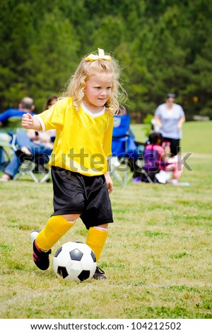 Cute young girl in uniform playing in organized youth league soccer game - stock photo