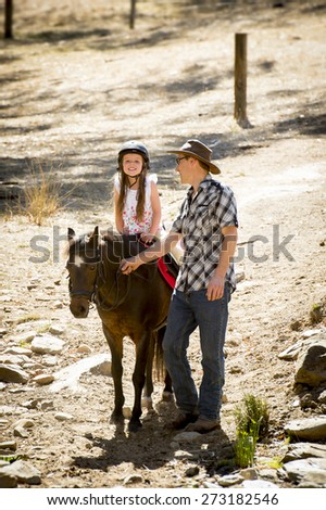 cute young girl jockey having fun riding pony outdoors happy with Australian American horse instructor in cowboy look teaching ride lesson in summer  nature countryside background