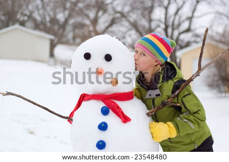 Cute Young Girl Kisses Snowman She Just Made - stock photo