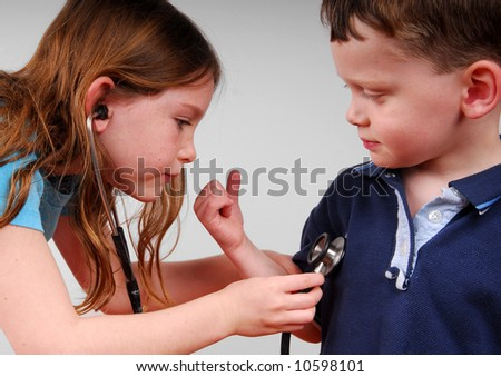 Cute young girl listening to cute young boy's heart - stock photo