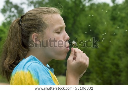 Cute young girl outside blowing dandelion seeds in the wind