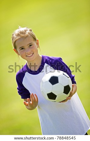 Cute young girl outside holding soccer ball.