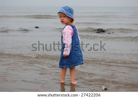 Cute young girl paddling in the sea.