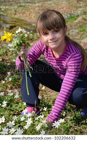 Cute young girl picking spring flowers in forest - stock photo