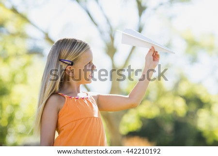 Cute young girl playing with a paper plane in park - stock photo