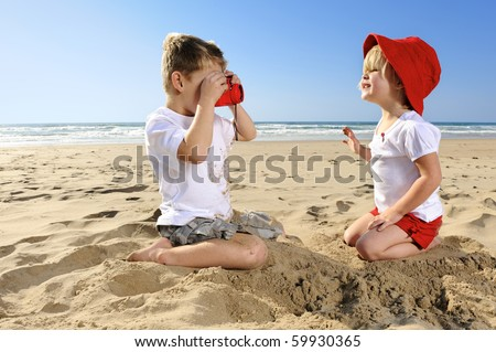 Cute young girl poses for her brother on the beach - stock photo