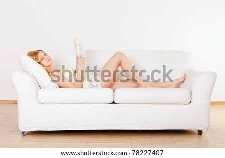 cute young girl reading on couch at home