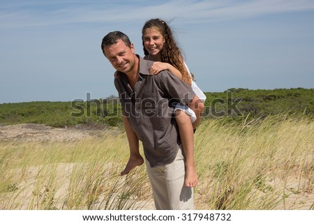 Cute Young Girl Rides Piggyback On Her Dads Shoulders Outside - stock photo