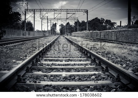 Cute young girl standing on a railroad - stock photo