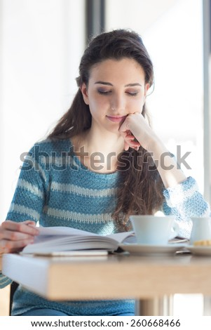 Cute young girl student at the cafe reading a book and sitting at the table - stock photo