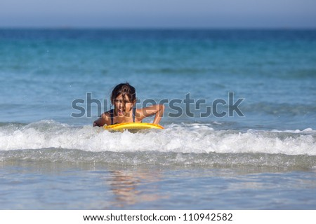 cute young girl surfs in the sea