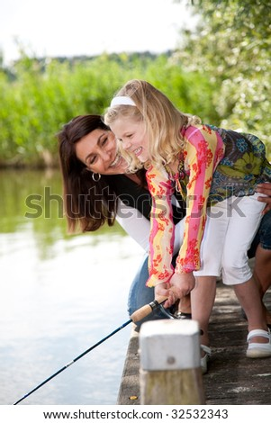 Cute young girl trying to catch a fish with mom watching over her - stock photo