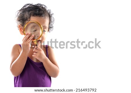 Cute young girl trying to use magnifying glass - stock photo