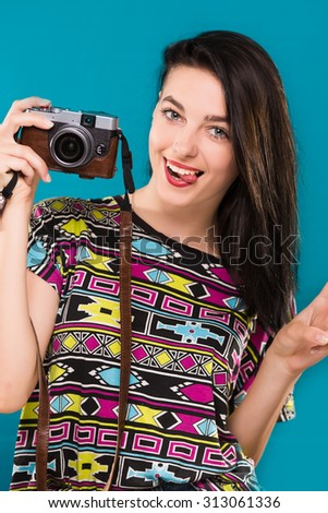 Cute young girl, with dark hair, wearing on colorful shirt, holding retro camera in her hand and smiling, on the blue background, in studio, waist up - stock photo