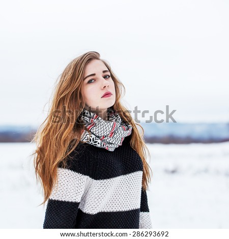 cute young girl with long hair in winter field - stock photo