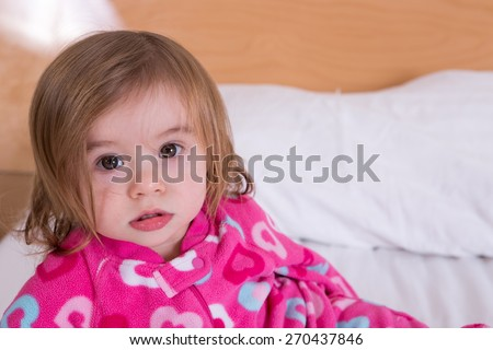 Cute young girl with tousled hair wearing pink pyjamas just awoken from her sleep giving the camera a wide eyed bemused stare