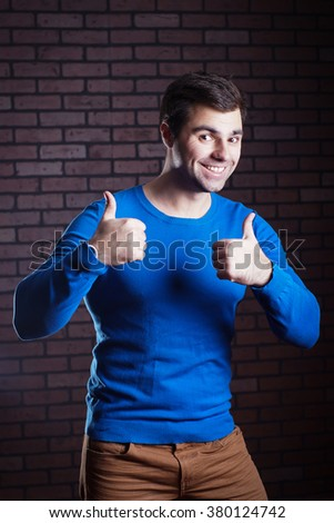cute young guy showing thumbs up - stock photo