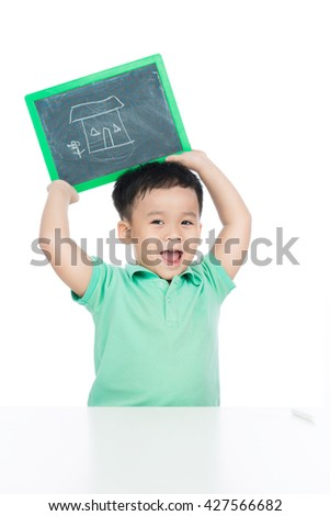 Cute young happy preschooler boy holding up black board with draw of a house for copy isolated on white - stock photo