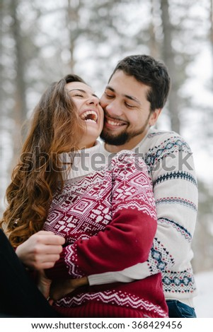 Cute young hipster couple having fun in winter park warming eachother on a bright day hugging each other and smiling