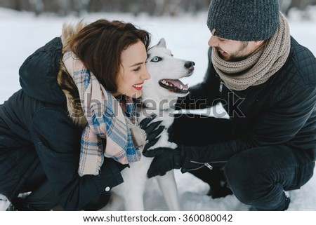 Cute young hipster couple having fun in winter park with their friend husky dog on a bright day hugging each other and smiling  - stock photo