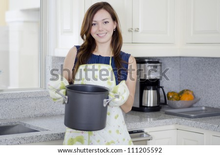 Cute young housewife boiling some water for dinner