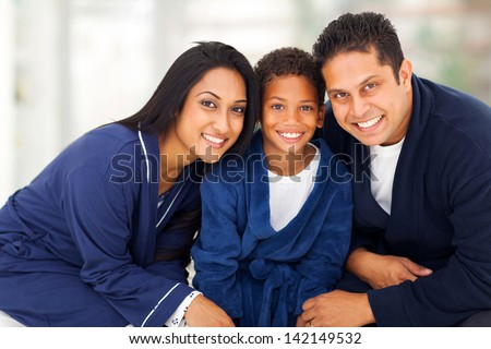 cute young indian family in their nightclothes sitting on bed - stock photo
