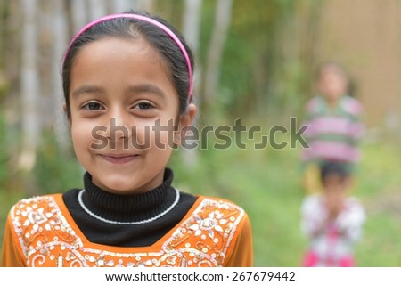 Cute young Indian girl smiling with soft green natural backdrop - stock photo