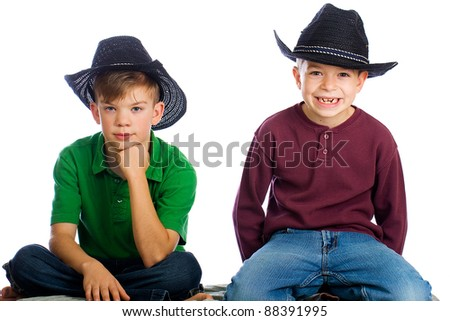 Cute young kids with happy smiles wearing cowboy hats. - stock photo