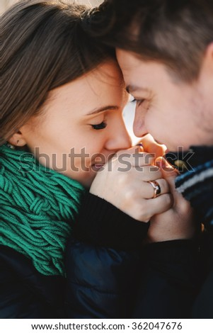 Cute young man and pregnant young woman having fun in winter park on a bright day hugging each other and smiling