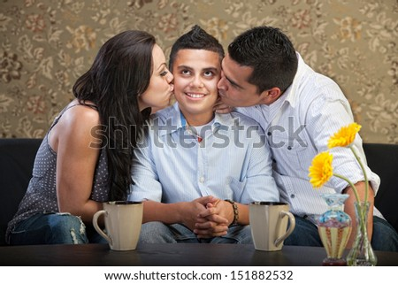 Cute young man being kissed by parents - stock photo