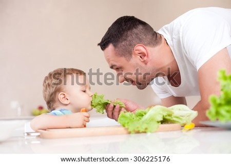 Cute young man is feeding his son with lettuce. He is looking at the toddler and smiling. The boy is eating vegetable with appetite. He is sitting at the table and holding a carrot - stock photo