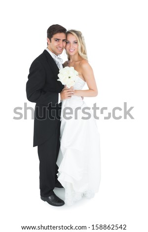 Cute young married couple posing holding a white bouquet smiling at camera - stock photo