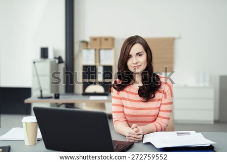 Cute Young Professional Woman Sitting at her Worktable with Laptop Computer, Documents and a Cup of Coffee While Looking at the Camera - stock photo