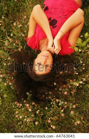 Cute young redhead female lying on grass field at the park