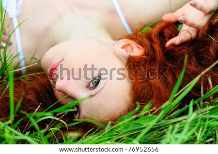 Cute young redhead female lying on grass field at the park. - stock photo