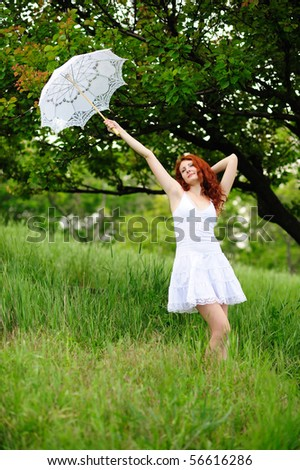Cute young redhead female standing on grass field at the park with umbrella - stock photo