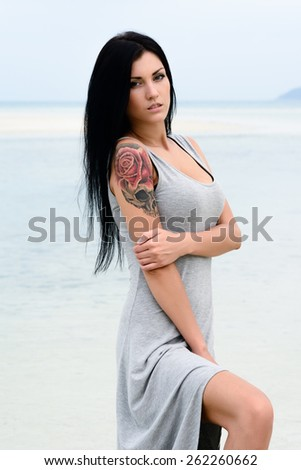 Cute young sexy girl in grey dress posing on the beach, blue sea background, brutal tattoo - stock photo