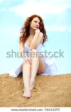 Cute young smiling female with red hairs sitting on ground - stock photo