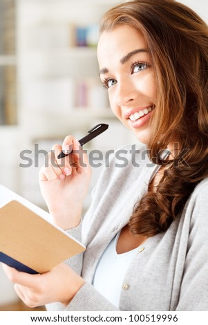 Cute young student thinking of success as she prepares for exams athome - stock photo