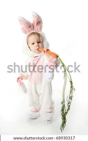 Cute young toddler girl wearing a bunny rabbit costume chewing on a carrot - stock photo