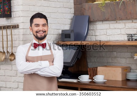Cute young waiter is working in restaurant. He is standing near the counter and smiling. The man is looking at the camera confidently - stock photo